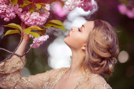 Sensual young woman standing in sexy transparent dress at blossoming pink sakura tree in the garden. Beauty of woman and nature.Portrait of beautiful model with curly blonde hair Archivio Fotografico