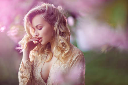 Sensual young woman standing in sexy transparent dress at blossoming pink sakura tree in the garden. Beauty of woman and nature.Portrait of beautiful model with curly blonde hair. Closed eyes in passion 写真素材