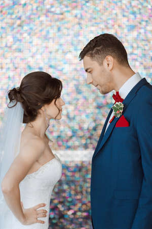 man in suite: Wedding couple in rage. Beautiful bride in white dress and veil with handsome groom in blue suite standing and angry in each other indoors against beautiful colored background bokeh. Close-up portrait of man and girl looking on each other in angry poses.
