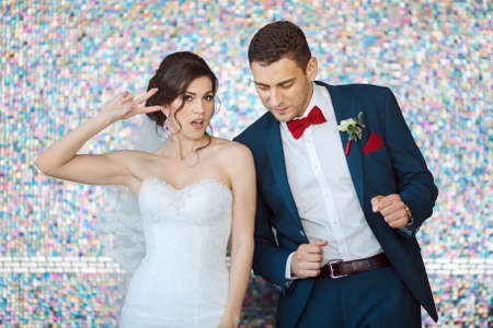 man in suite: Wedding couple in love. Beautiful bride in white dress and veil with handsome groom in blue suite dancing and having fun indoors against beautiful colored background bokeh like their good mood. Close-up portrait of man and girl in fanny poses
