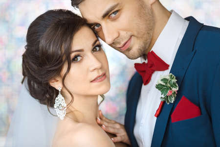 man in suite: Wedding couple in love. Beautiful bride in white dress and veil with handsome groom in blue suite standing and embracing each other indoors against beautiful colored background bokeh like their dreams. Close-up portrait of man and girl looking at camera