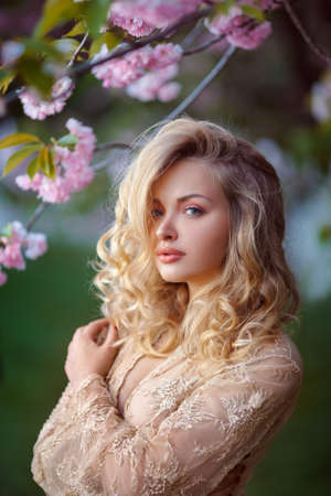 transparent dress: Sensual young woman standing in sexy transparent dress at blossoming pink sakura tree in the garden. Beauty of woman and nature.Portrait of beautiful model with curly blonde hair Stock Photo