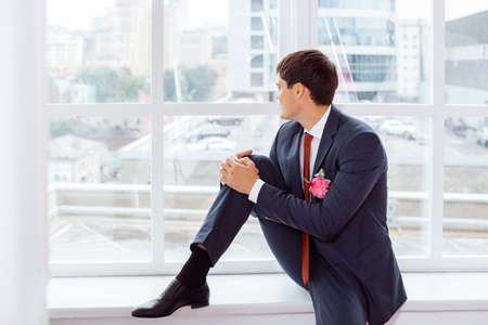 man in suite: Gorgeous smiling groom. Handsome man in a suite with a buttonhole sitting on window sill and lookin in window indoors Stock Photo