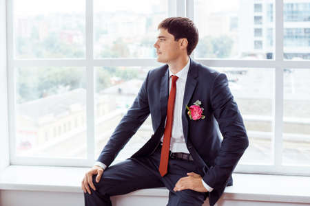 man in suite: Gorgeous smiling groom. Handsome man in a suite with a buttonhole sitting on window sill indoors Stock Photo