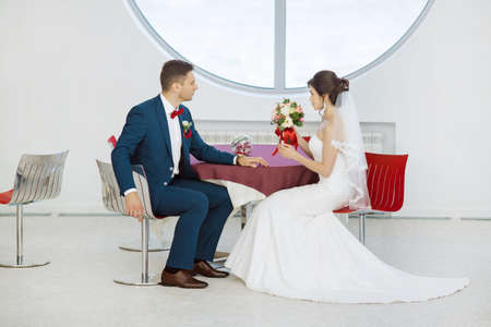 full lenght: Wedding couple in love. Beautiful bride in white dress and veil and brides bouquet with handsome groom in blue suit sitting in cafe. Full lenght portrait of man and girl. Concept of wedding celebration in vacation