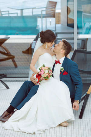 full lenght: Wedding couple in love. Beautiful bride in white dress and veil and brides bouquet with handsome groom in blue suit sitting on plank bed and embracing each other indoors at pool. Full lenght portrait of man and girl. Concept of wedding celebration in vaca Stock Photo