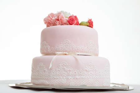 Roze bruidstaart met rozen tegen een witte achtergrond geïsoleerd