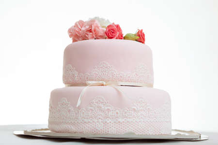 Pink wedding cake with roses against  white isolated background