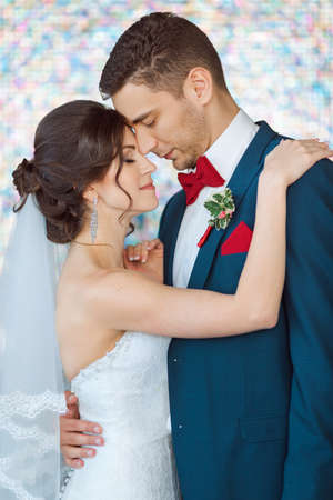 man in suite: Wedding couple in love. Beautiful bride in white dress and veil with handsome groom in blue suite standing and embracing each other indoors against beautiful colored background bokeh like their dreams. Close-up portrait of man and girl with closed eyes