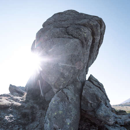 scrambling: View of the high mountains with big rock on the foreground. Rays of the sun. Square shot Stock Photo