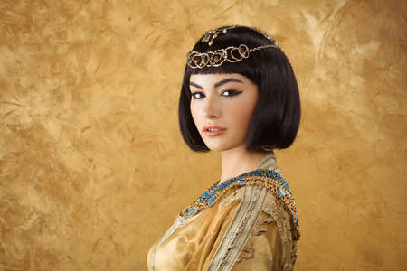 Photo of gorgeous woman with Cleopatra makeup, closeup portrait of beautiful female with stylish haircut agaist golden background, young lady wearing fashionable golden necklace, beauty salon Foto de archivo