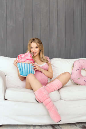 woman ice cream: Beautiful pregnant woman looking at camera and smiling sitting on a couch. The happiest time for every woman. Ice cream and doughnut in the hands of a pregnant girl Stock Photo