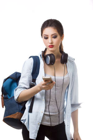 high spirited: Portrait of happy teenager girl with school backpack and earphones smartphone isolated on white background. Happy woman in casual clothing. Good for sports and travel concept