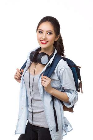 Portret van gelukkig tienermeisje met schoolrugzak en oortelefoons die op witte achtergrond wordt geïsoleerd. Gelukkige vrouw in vrijetijdskleding. Goed voor sport en reizen concept