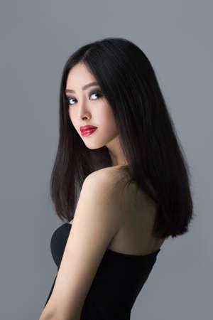 어두운 회색 격리 된 배경에 긴 머리를 가진 아름 다운 젊은 아시아 여자 스톡 콘텐츠