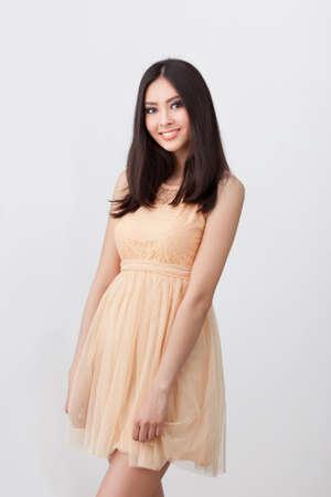 Prachtige vrouw. Portret van mooie lachende jonge vrouw staan in schattige beige kleding die op een grijze achtergrond. Sexy gemengd ras Chinese Aziatische Kaukasische vrouwelijke model. Stockfoto