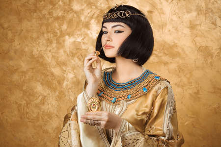 Young girl with perfume bottle. Glamorous closeup portrait of beautiful sexy stylish brunette young woman model with bright makeup with gold jewelery. Cleopatra