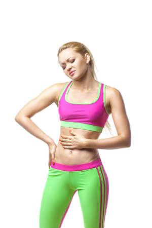 Stomach pain. Sport woman having abdominal pain, upset stomach or menstrual cramps. Pain in the abdomen, close-up over white isolated background Stock Photo