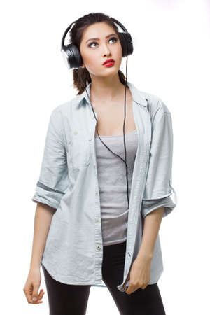 conceive: Music. Relaxed woman with big earphones headphones listening to music on mp3 player. Young mixed race Asian Caucasian woman isolated on white background.