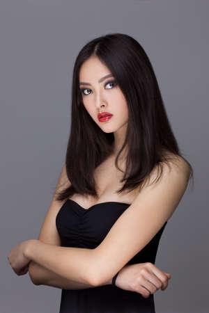 Mujer asiática joven hermosa con el pelo largo en el fondo aislado gris oscuro Foto de archivo - 60567076