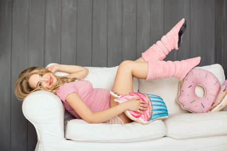 woman ice cream: Beautiful pregnant woman looking at camera and smiling lying on a couch. The happiest time for every woman. Ice cream and doughnut in the hands of a pregnant girl Stock Photo
