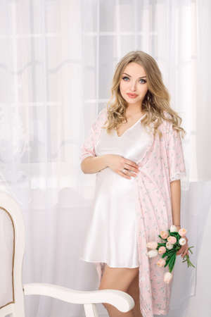 nightgown: Portrait of beautiful pregnant woman. Blonde girl holding flowers posing in nightgown lovely looking at camera in white room. Indoor shot against window.