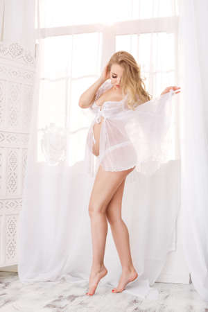 Portrait of beautiful pregnant woman. Blonde girl posing in transparent dressing gown in full length and white underwear lovely looking at belly in white room. Indoor shot against window.