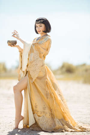 Woman pours potion, poisons water. Fashion Stylish Beauty Portrait Holding and Drinking Cup. Girl standing in golden dress outdoors in desert. Hot sunny weather Standard-Bild