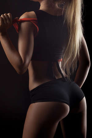 Sweaty woman having a break in a gym showing her well trained body, buttocks. Mesomorph Body Type. Girls silhouette studio photo against black background
