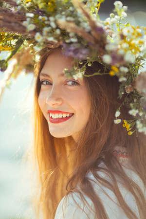 Smily Porträt der schönen Mädchen in Kranz aus Blumen in der Wiese an einem sonnigen Tag. Portrait der jungen schönen Frau, die einen Kranz von wilden Blumen tragen. Junge heidnischen slawischen Mädchen Verhalten Zeremonie auf Midsummer. Tag der Erde