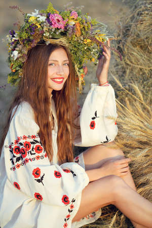Beautiful smiling girl in wreath of flowers in meadow on sunny day. Portrait of Young beautiful woman wearing a wreath of wild flowers. Young pagan Slavic girl conduct ceremony on Midsummer. Earth Day