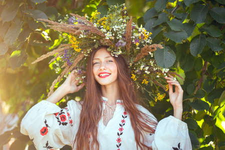 beautiful girl in wreath of flowers in meadow on sunny day. Portrait of Young beautiful woman wearing a wreath of wild flowers. Young pagan Slavic girl conduct ceremony on Midsummer. Earth Day Archivio Fotografico