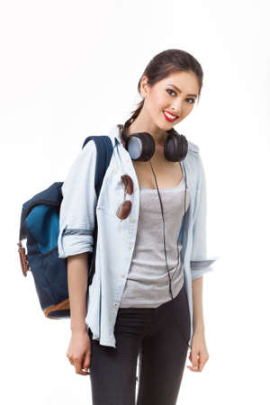 high spirited: Portrait of happy teenager girl with school backpack and earphones isolated on white background. Happy woman in casual clothing. Good for sports and travel concept