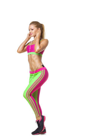 mp3 player: Walking fitness woman with earphones isolated. Female runner in sporty pink and green fitness outfit jogging isolated on white background. Beautiful mixed race Asian Caucasian fitness model training. Stock Photo
