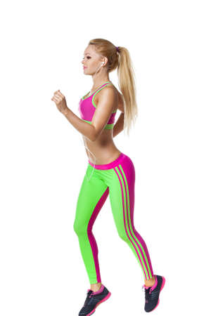 musik: Running fitness woman with earphones isolated. Female runner in sporty pink and green fitness outfit jogging isolated on white background. Beautiful mixed race Asian Caucasian fitness model training.