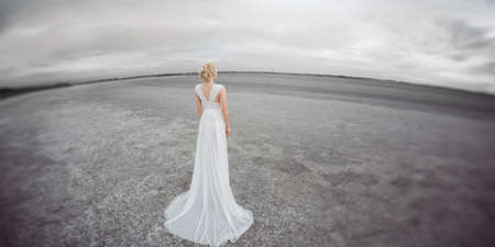 fish eye lens: Bride outdoors in a desert looking afar. Beautiful woman in white dress full body length. Stretched wide landscape fish eye lens photo. Gray background copy space good for texting. Some fine art noise.