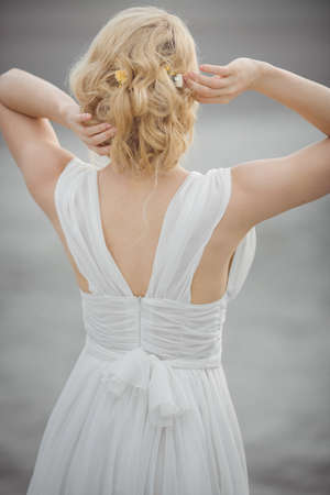 bridal hair: Back-view bridal hair style. Beautiful bride in white dress. Stock Photo