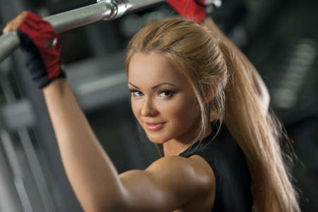 Fitness portrait of a young woman, abs close up. Girl doing back pullups at the gym, and looking at camera
