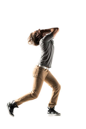 Young man dancer dancing funky hip hop rnb on isolated studio white background. Full length silhouette. Stock Photo