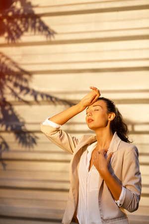 Tijd om te reizen concept. Openlucht de zomerportret van jong vrij leuk donkerbruin meisje die de zomerhitte lijden. Mooie vrouw bij straat tegen de bedrijfsbouw met schaduw van palm in hete dag in de stad.