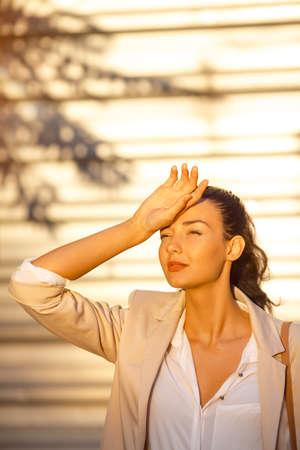 Zeit zu reisen Konzept. Outdoor-Sommer-Porträt der jungen ziemlich niedlich gleichaltrige Mädchen Leiden Sommerhitze. Schöne Frau auf der Straße gegen Geschäftsgebäude mit Schatten der Palme in heißen Tag in der Stadt.