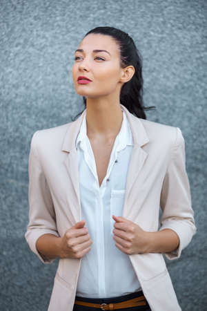 Beautiful brunette business woman in suit standing outdoors against gray background and looking away. Copy space