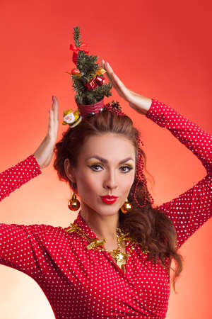 efforts: New Years and Christmas efforts and preparations. Girl with New Year tree instead of santa hat on head thinks about winter holidays celebration. Woman arranging decorations of Xmas tree. Creative fun studio photo.