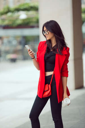Young pretty businesswoman texting outdoors. Beautiful young stylish asian woman in red casual suite and glasses with phone and cup of coffee against street background