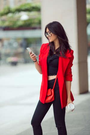 Jonge mooie onderneemster die in openlucht texting. Mooie jonge stijlvolle Aziatische vrouw in rode casual suite en glazen met telefoon en kopje koffie tegen straat achtergrond