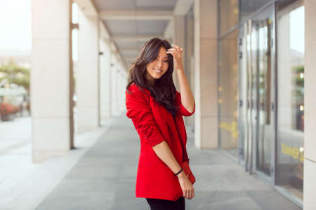 Happy asian woman standing outdoors in business casual red suite against mall Stock Photo
