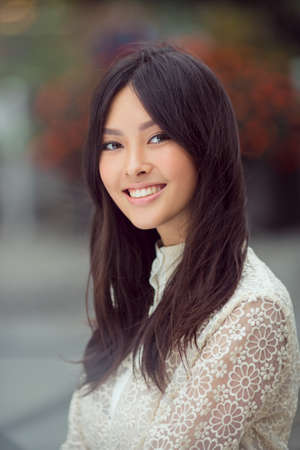 Donna sorridente - ritratto di felice razza mista asiatico giovane donna caucasica bella e bella esterna contro città offuscata bokeh Archivio Fotografico - 67649201