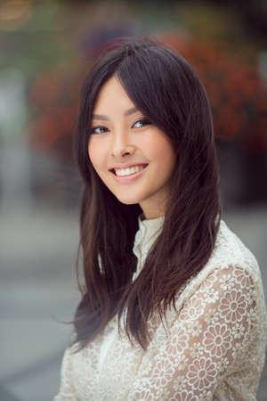 Vrouw lachend - Portret van gelukkige mooie en mooie halfbloed Aziatische blanke jonge vrouw buiten tegen de stad vaag achtergrond