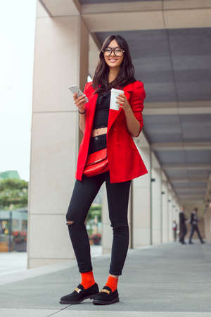 full lenght: Young pretty businesswoman texting outdoors. Beautiful young stylish asian woman in full lenght in red casual suite and glasses with phone and cup of coffee smiling and looking at camera against street background Stock Photo