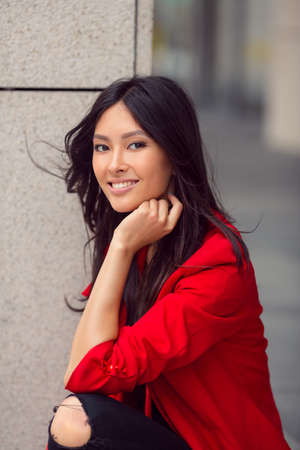 lovely businesswoman: Woman smiling - portrait of happy lovely and beautiful mixed race Asian Caucasian young businesswoman in casual clothes outdoor sitting on steps